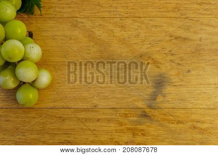 background from a brown old oak barrel with green grapes