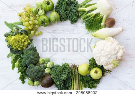 Top view of green vegetables and fruits arranged in a frame, copy space for text in the middle, selective focus