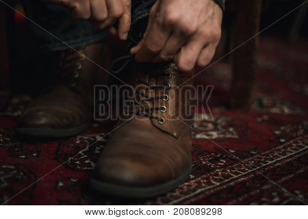 Closeup of male hands lacing up and tying his old brown leather boots.