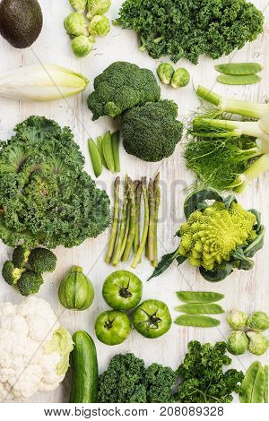 Assortment of green vegetables on the white wooden table arranged in a grid, vertical, top view, selective focus
