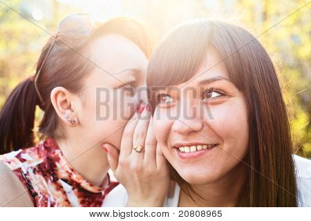 Young Beautiful Woman Whispers Something To Girlfriend In Her Ear