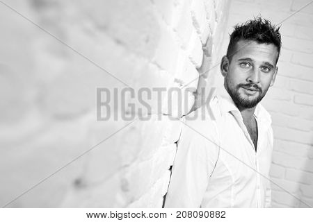 Black and white portrait of goodlooking young caucasian man wearing white shirt standing at wall.