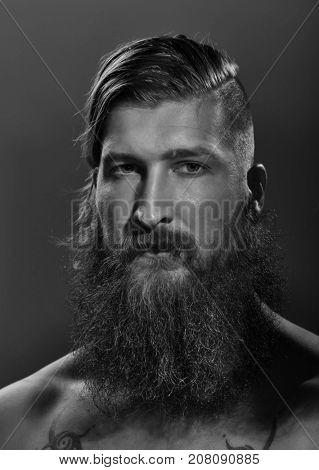 Black and white portrait of a young serious bearded man looking at camera.