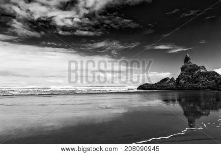 Reflection of rocks in the wet sand on the beautiful Piha beach near Auckland, New Zealand. Dramatic balck and white