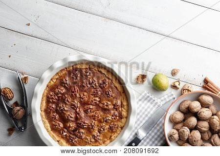 Traditional walnut pie with nuts and nutcracker on white wooden planks, top view