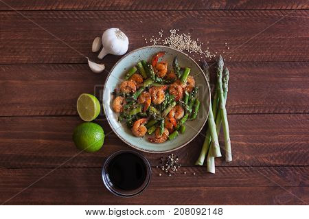 Asian salad with asparagus and shrimps in plate on the dark wooden background