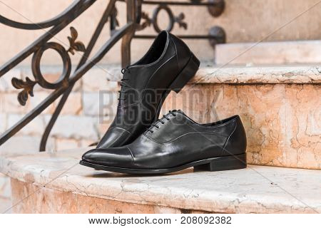 Black dress shoes men on the steps the pink marble staircase