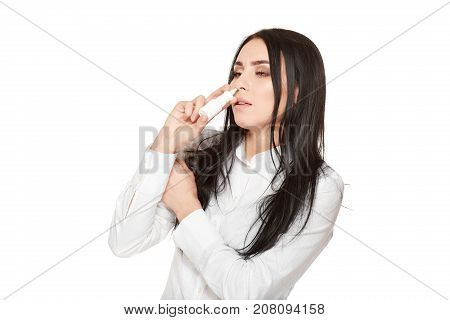 Portrait of unhealthy young girl drown droplets or nasal spray in nose from bottle with medicament. Illness woman with flue in autumn and winter time. Respiratory and virus symptoms. Isolate.
