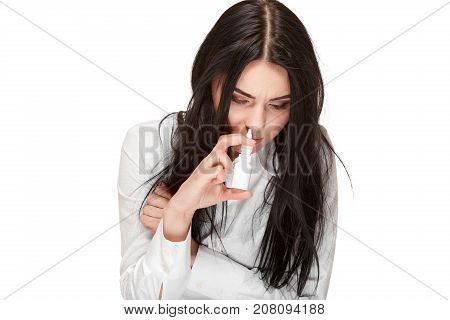 Portrait of unhealthy brunette girl using and drown spray for nose, anti virus, flu medicament. Illness, virus, respiration and care with this problem.  Autumn infection. Isolate on white.