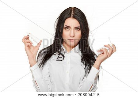 Portrait of angry and sadly brunette woman looking at camera, with arms up with two  bootless of nasal spray. Permanent method for flu and illness. Medicament for allergy.