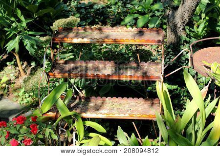 Old, rusty shelving sitting in a garden on a bright sunny day.