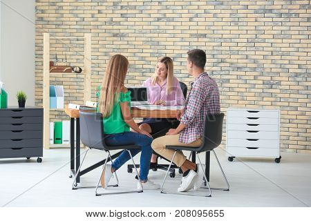 Real estate broker and customers discussing buying of new flat in office