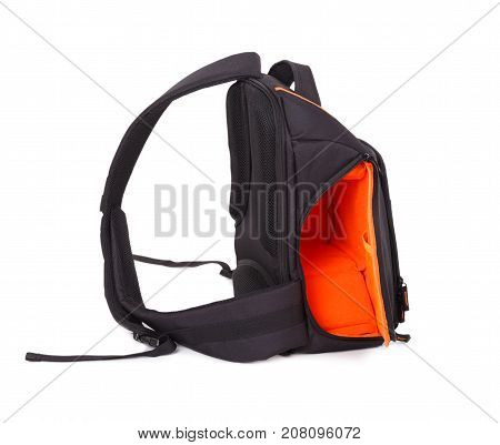 Outdoor backpack for camera isolated on white background. Outside is black, inside is orange. Turned left side. Close-up.