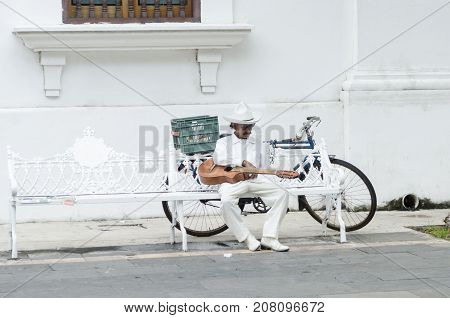 VERACRUZ, MEXICO- SEPTEMBER 27, 2017: Musician dressing with traditional jarocho clothes resting on a bench at the street in Veracruz, Mexico