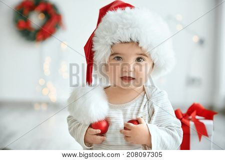 Little baby in Santa hat with Christmas balls on blurred background