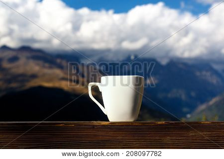 White cup of coffee and tea with steam on wood table over mountains landscape. Beauty nature background.