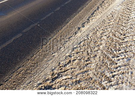a dirty trail on which traces of the car were imprinted. Photo taken in the winter season.