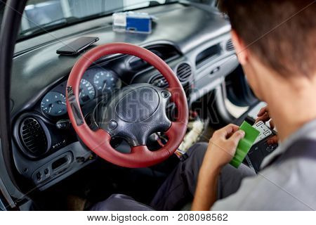 The mechanic sitting in the car conducts diagnostics of electronics with the help of special devices and tablets
