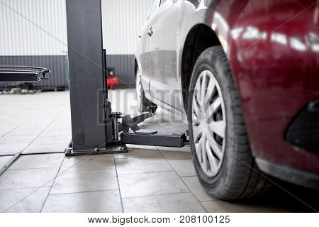 Lifted cars on the lift in a car service for diagnosis