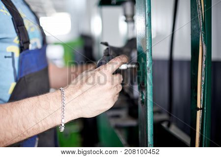 The mechanic sharpens the part on the machine for further installation on the car
