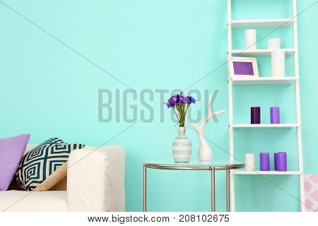 Lilac accent in modern interior. Table with flowers in living room