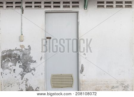 The dirty restroom door and old wall peeling texture beside switch lighting