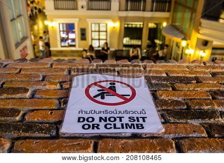 Sign - Do not sit or climb on the wall