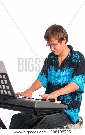 A teenage boy seated at a keyboard playing. Isolated against a white background.