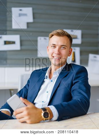 Joyful business man holding a smatrtphone on a blurred office background. Modern enterpreneur in a formalwear with a mobile.