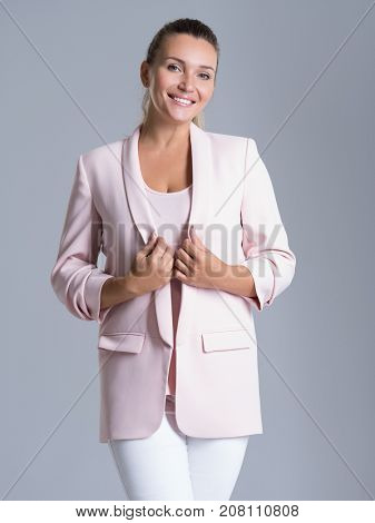 Portrait of a happy friendly smiling woman over white background. Pretty young adult female in pink jacket and white trousers