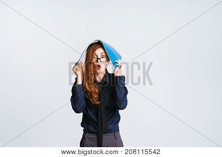 young secretary girl in a black shirt is surprised to hold a folder over her head