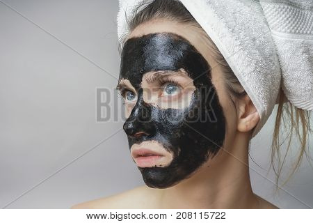 Black mask on woman face, smiling, skincare, cleansing pore ,against acne