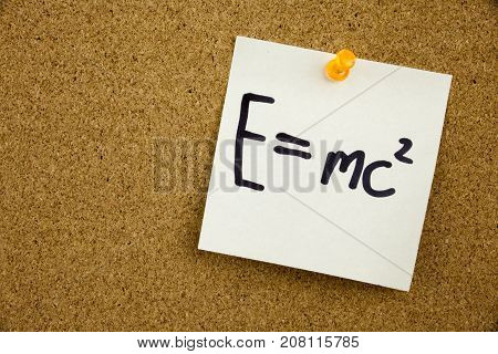 A Yellow Sticky Note Writing, Caption, Inscription Equation E Equal Mc2 In Black Ext On A Sticky Not