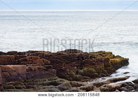 A rocky outcrop jutting into the Atlantic Ocean. The rocks have sea weed on them. Photographed in natural light in Acadia National Park Maine.