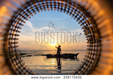 Silhouette of asian fisherman on wooden boat fisherman in action throwing a net for catching freshwater fish in nature river