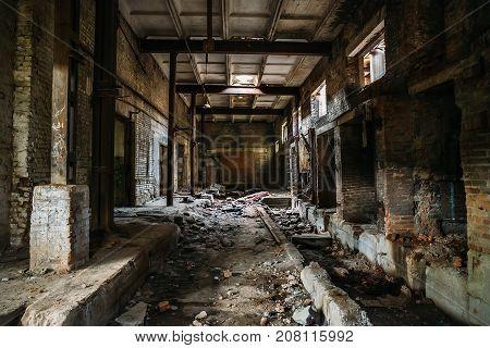 Dark scary corridor in abandoned industrial ruined brick factory, creepy interior, perspective toned