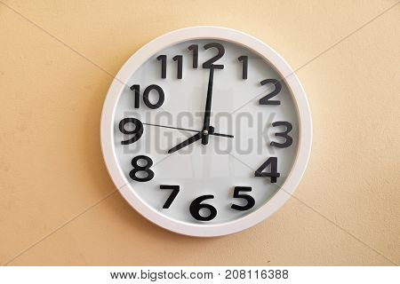 Wall clock running time on cream color background.