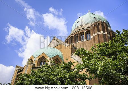 BRUSSELS BELGIUM - JUNE 19 2016: Detail of the facade of the Basilica of The Sacred Heart in Koekelberg with the two domes and trees in the foreground in a sunny day with clouds. Brussels Belgium.