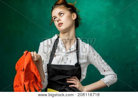 tired girl after cleaning in a black apron removes gloves