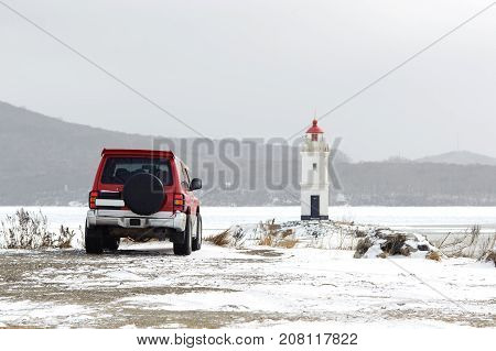 Red car in front of lighthouse on the seacoast in snowy winter day