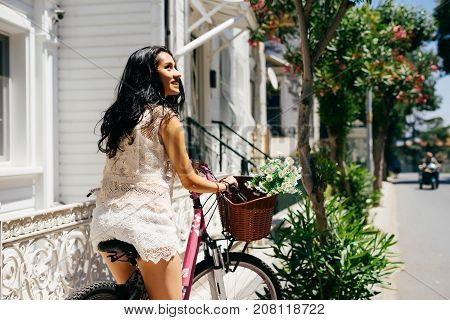 Hot tropical summer background with woman cycling on pink bike, copy space
