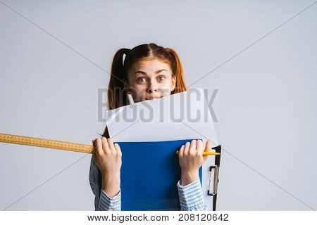 girl student with surprised expression holds folders folders