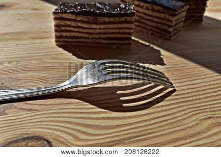 Silver fork at wooden background whit chocolate cookie behind