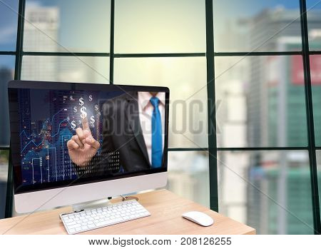 the computer on the wood table with Businessman point sign of money on the trading graph at the screen in front of the glass window over the blurred photo of cityscape background, 3D