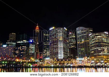 SYDNEY AUSTRALIA - AUGUST 2017 : View of Sydney city skyline at night near Pyrmont Bridge Cockle Bay Wharf in Sydney Australia on August 14 2017.