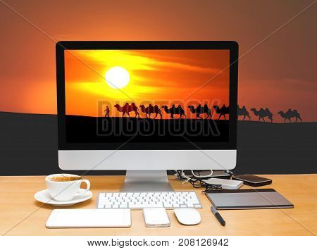 Conceptual image of a workspace with computer desktop on camel caravan with sunset background