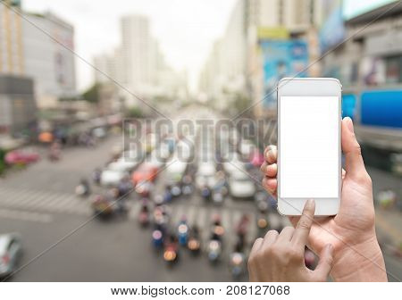 Female hand holding mobile smart phone on abstract Blurred photo of traffic jam with rush hour