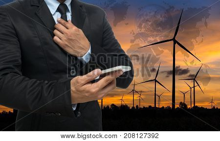 Businessman using the tablet with stack of golden coins on Wind turbine power generator at twilight timeElements of this image furnished, 3D illustration