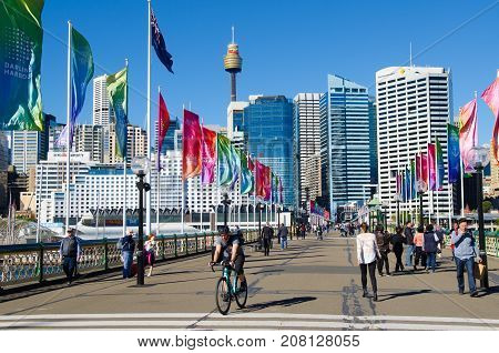 SYDNEY - AUGUST 18 2017:People crossing the Pyrmont Bridge at sunset in Darling Harbour a recreational and pedestrian precinct western to Sydney central business district in New South Wales Australia