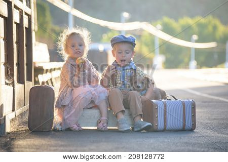 Small boy and girl eating apples outside, sitting on suitcases in vintage outfit, with dog nearby, waiting for a train on railroad station, ready to travel